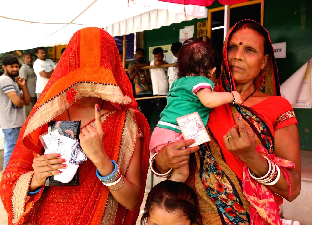 Women show their voter identity card at a polling booth during the sixth phase of 2019 Lok Sabha elections, in New Delhi on May 12, 2019.