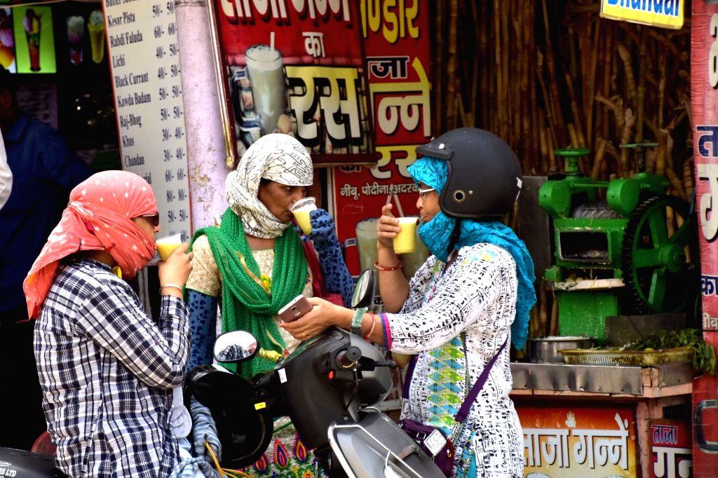 Women sip sugarcane juice to beat the heat in Jaipur, on May 27, 2017.