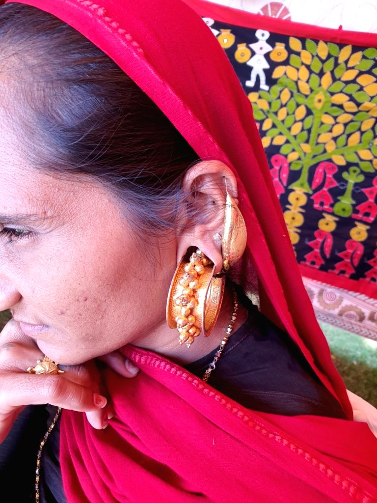 Women sitting with their ears adorned with big pretty earrings pierced into quite a big-sized ear hole (of around 2-3 inch) and their complete arms and hands heavily tattooed with little ...