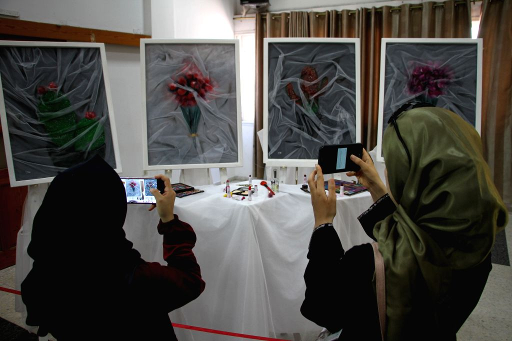 Women take photos at Palestinian artist Kholoud El-Desouki's exhibition, describing the feelings of women in Gaza Strip, in Gaza City, Aug. 11, 2020. - Kholoud E