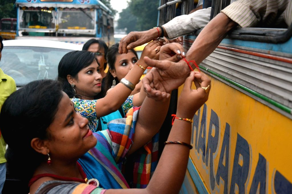 Women tie friendship bands to passengers in bus on Friendship Day in Kolkata on Aug 5, 2018.