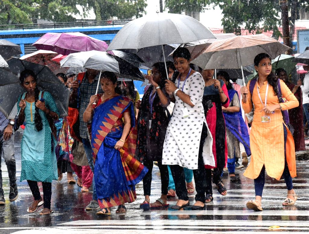 Women use umbrella to shield themselves from rains in Kochi, Kerala on July 18, 2019.