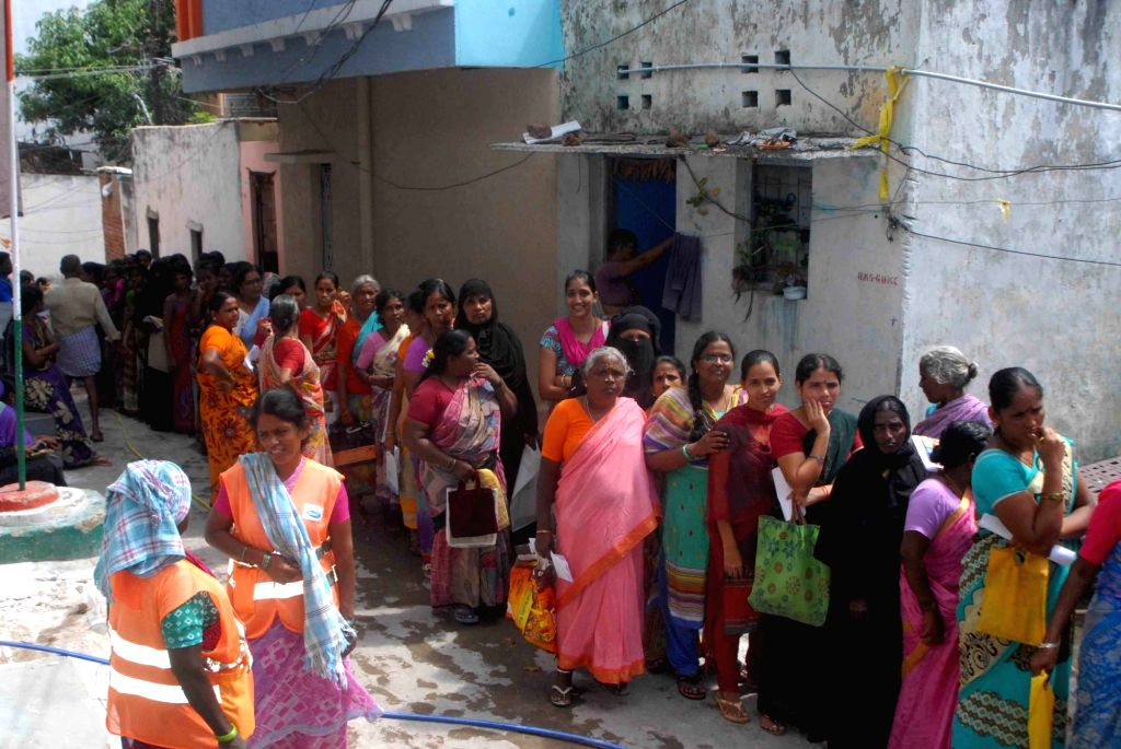 Women wait in queues during the distribution of free sarees as a Bathukamma flower festival gift in Hyderabad on Sept 19, 2017.