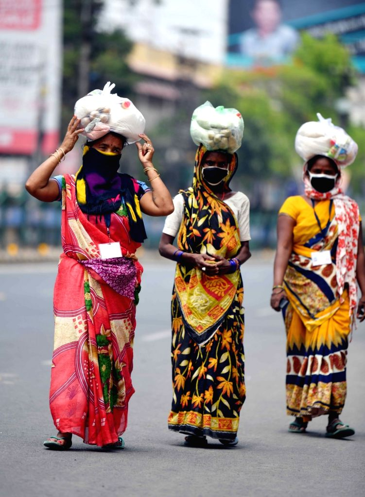 Women walk back home carrying vegetables and other essentials on their head in Patna during the extended nationwide lockdown imposed to mitigate the spread of coronavirus; on Apr 25, 2020.