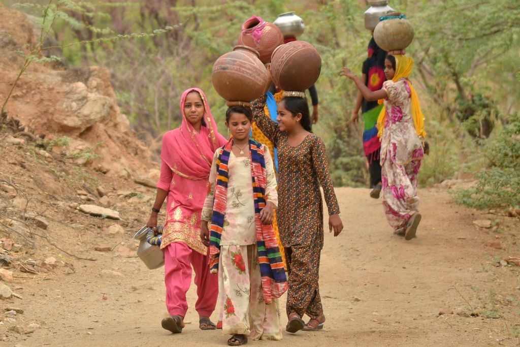 Women walk back to their homes after collecting drinking water from the outskirts of Ajmer amid scarcity of drinking water, on June 13, 2019.