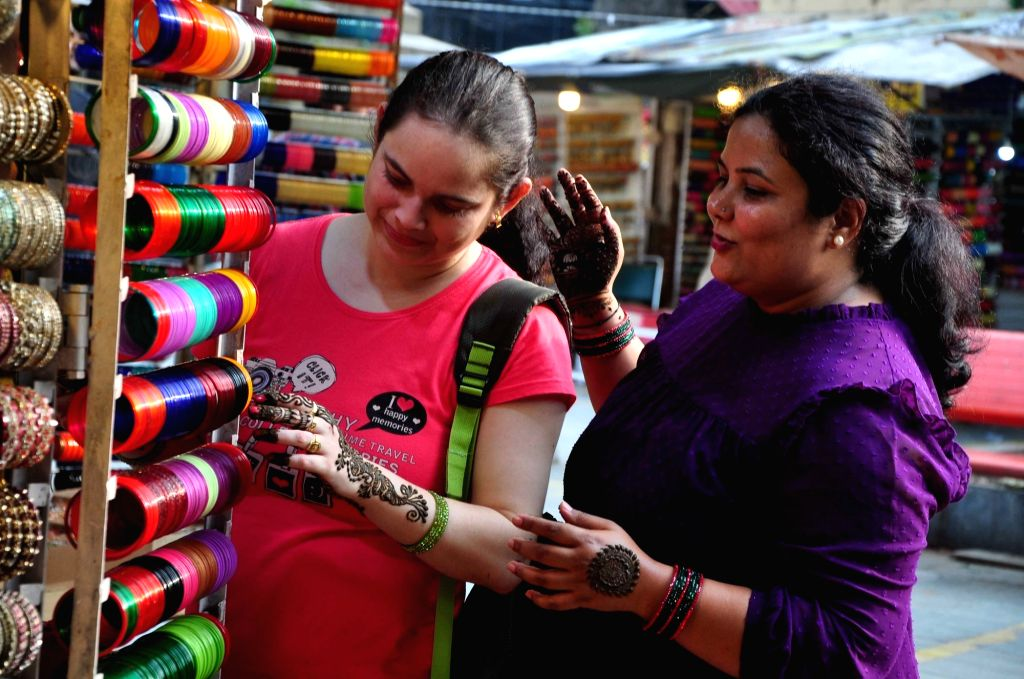 Women with their palms decorated with 'henna', shop for bangles during  'Teej' celebrations in New Delhi on Aug 3, 2019.