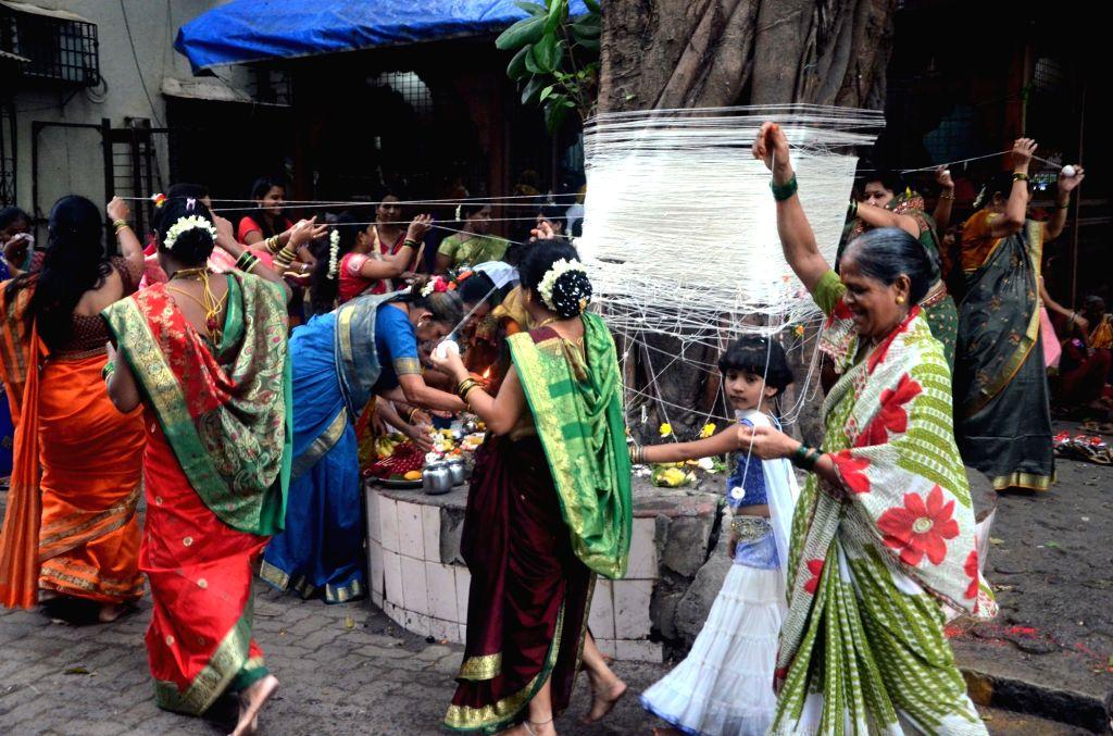 Women worship a tree during Vat Savitri puja at Dadar in Mumbai on June 19, 2016.