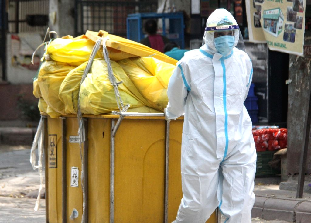 Worker of Lok Nayak Jai Prakash Hospital (LNJP) wearing PPE suits during the Biometric wastage (BMW) dump at LNJP (BMW) storage area in New Delhi on Monday, 10 May, 2021.
