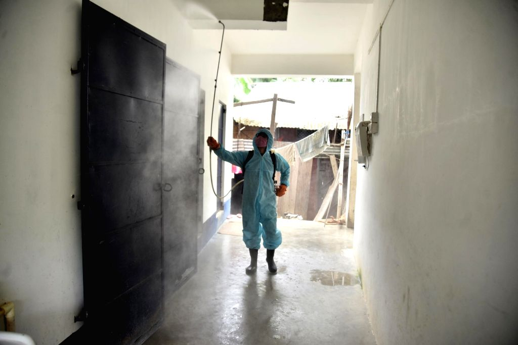 Worker wearing personal protective equipment (PPE) sprays disinfectant to sanitize a School to prevent the spread of the coronavirus disease (COVID-19) in Nagaon District of Assam on August ...