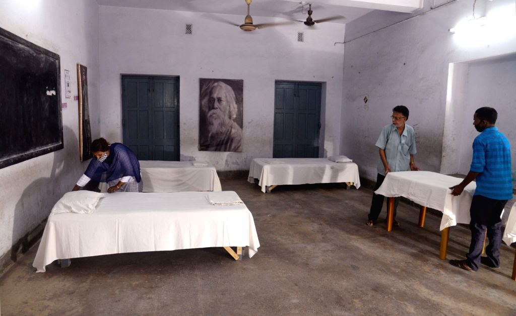 Workers arrange beds at a State run school Kamala Chatterjee School which was converted into a quarantine center due to the surge of COVID 19 cases across the State  in Kolkata   23 May, ... - Kamala Chatterjee School