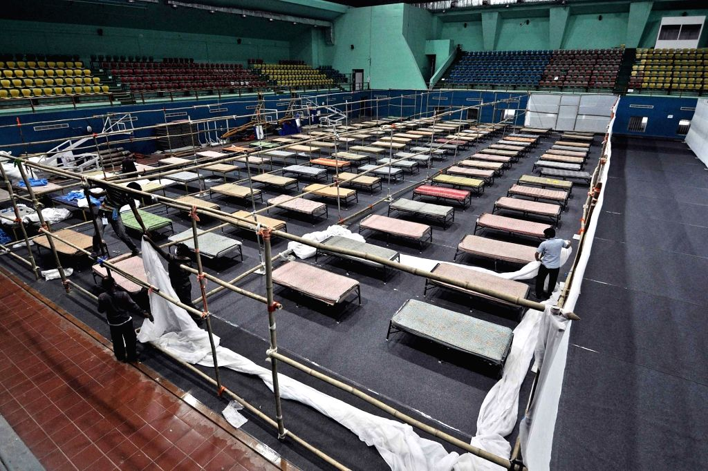 Workers busy arranging beds at the quarantine centre at Sarusajai Sports Complex on Day 6 of the 21-day countrywide lockdown imposed to contain the spread of novel coronavirus, in Guwahati ...
