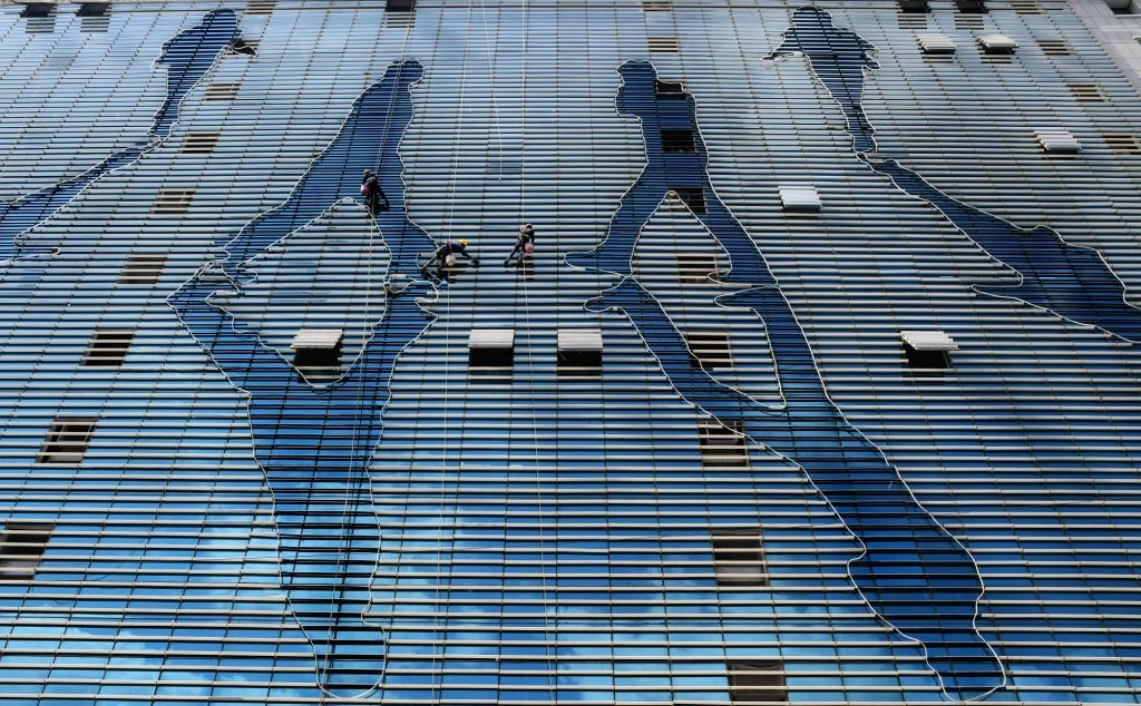 Workers busy cleaning a building at Andheri in Mumbai.