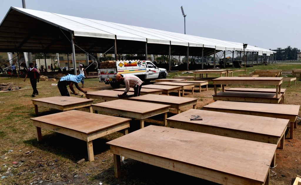 Workers busy making beds for a 1000-bed quarantine facility at the Sarusajai sports complex during the nationwide lockdown imposed in the wake of the coronavirus pandemic, in Guwahati on ...