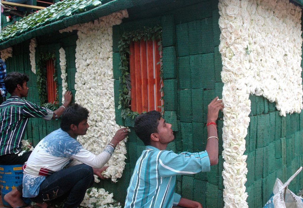 "Workers busy making the floral replica of Kannada poet Rashtrakavi Kuvempu's house ""Kavishala""using Dutch White and Red roses underway ahead of the upcoming Independence Day Flower ..."