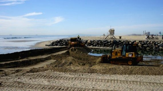 Workers drive heavy machinery to build a berm to prevent oil spill in Orange County, California, Oct. 3, 2021.