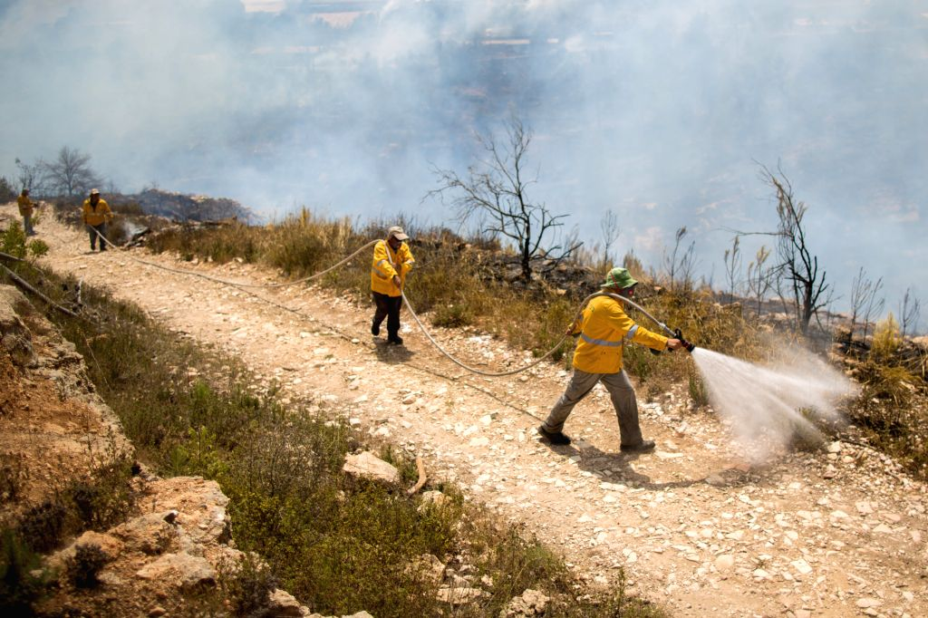 Workers from the Israel Nature and Parks Authority (INPA) try to quench the hotspots caused by a conflagration raging in Even Sapir on the outskirts of Jerusalem, ...