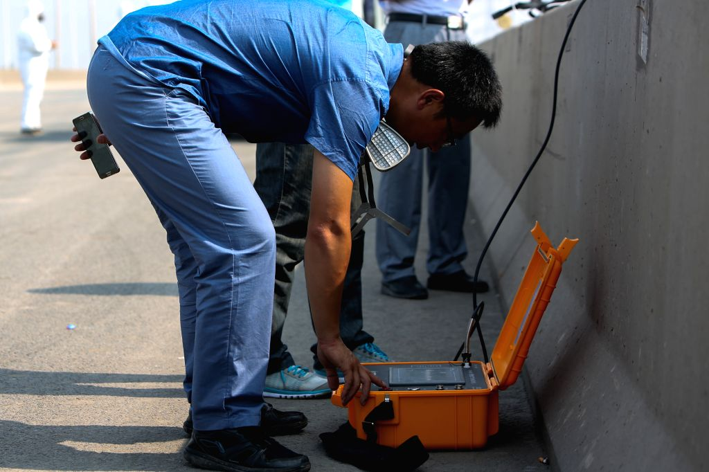 Workers monitor the air condition near the explosion site in north China's Tianjin Municipality, Aug. 16, 2015. A total of 112 bodies have been found, and 95 people ...