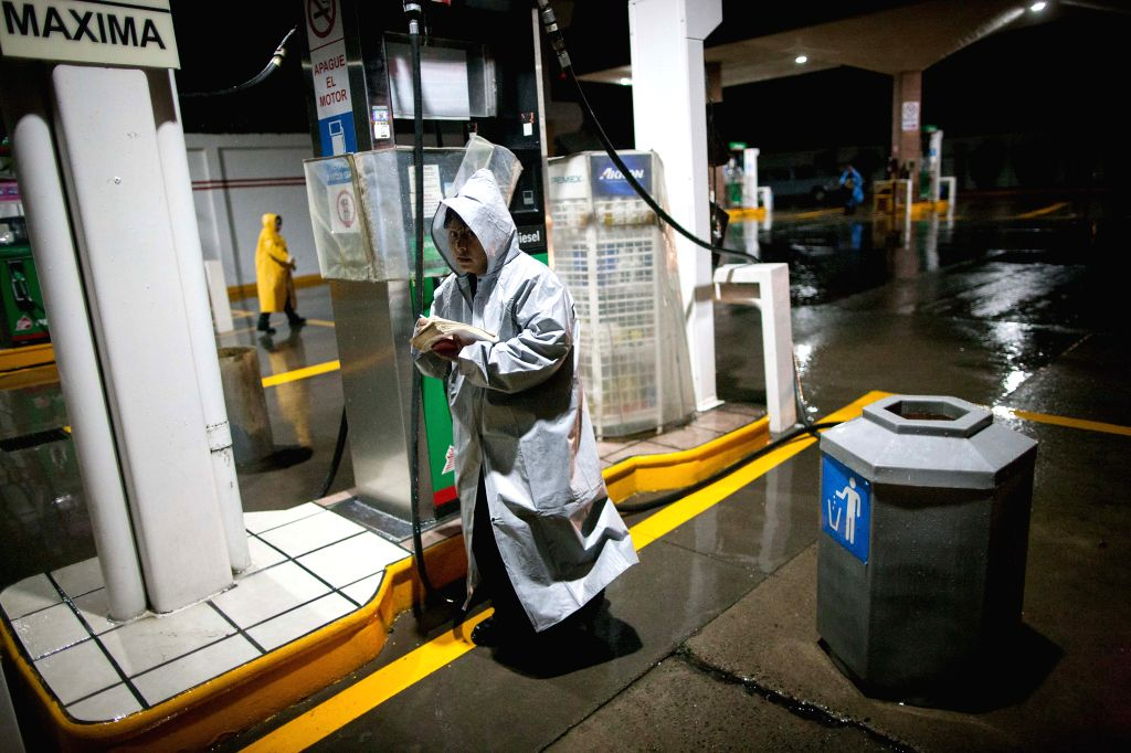 """Workers of a gas station prepare for the arrival of hurricane """"Patricia"""" in Ameca, Jalisco state, Mexico, on Oct. 23, 2015. An hour after Hurricane Patricia ..."""