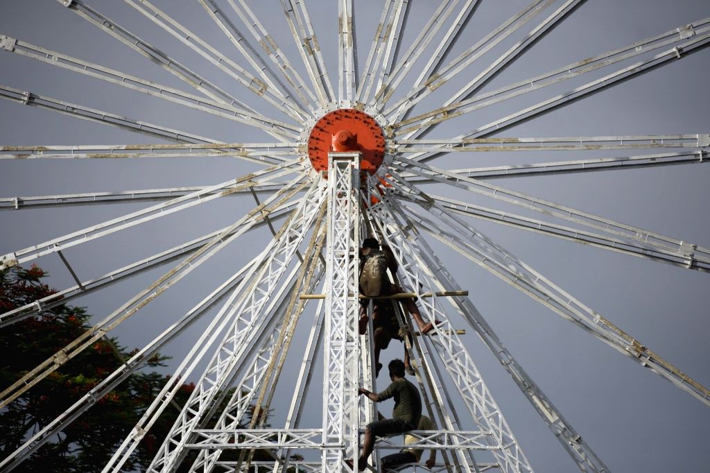 Workers tighten bolts of a Ferris wheel at a fair ground in Nagaon on June 14, 2019.
