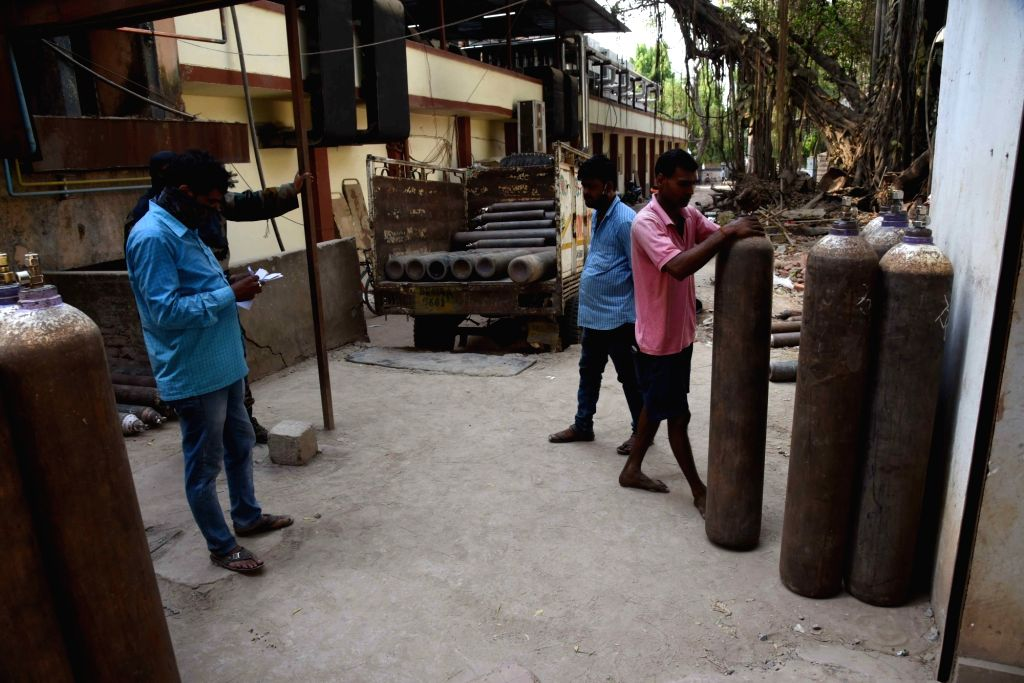 Workers unload oxygen cylinders for COVID-19 patient at Patna Medical College and Hospital (PMCH), amid the rise in Covid-19 cases across the Country, in Patna, On Thursday, 22 April, 2021.