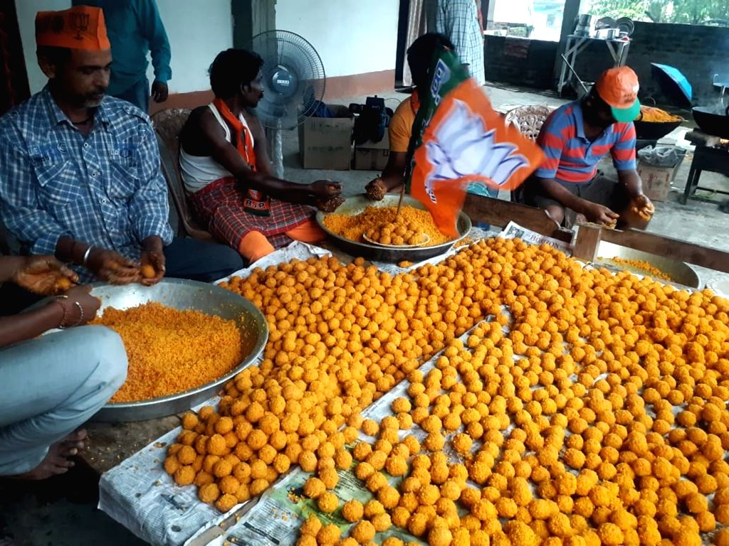 Workers wearing BJP caps busy preparing laddus -sweets- at a workshop on the eve of counting for 2019 Lok Sabha polls in Dibrugarh, Assam on May 22, 2019.