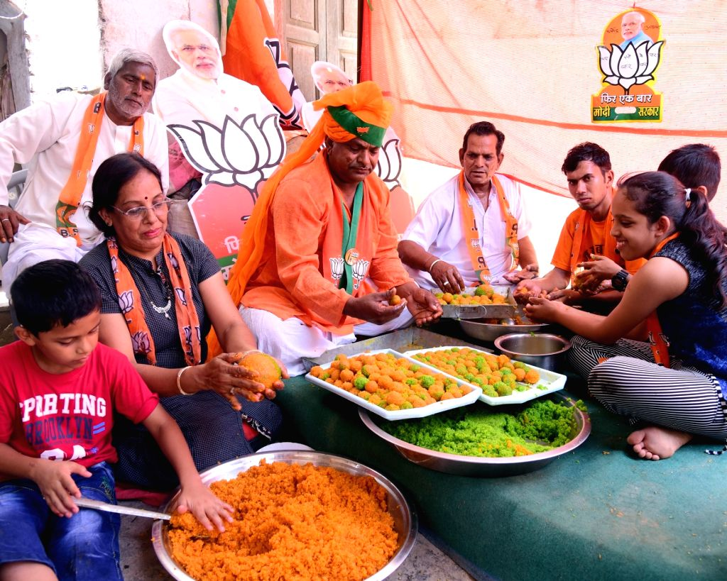 Workers wearing BJP scarves busy preparing 'Laddus' - sphere-shaped sweets - on the eve of the counting of votes for 2019 Lok Sabha elections, in Bikaner on May 22, 2019.