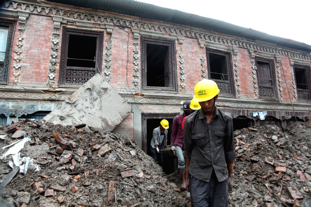 Workers work at a building which was destroyed by the April 25 devastating earthquake, in Sankhu, on the outskirts of Kathmandu, Nepal, Aug. 15, 2015. ...