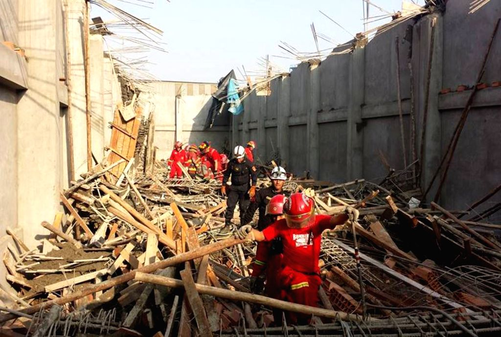 Workers work at the site of a ceiling collapse accident in Lima, Peru, on Aug. 10, 2015. According to local press, 10 people were injured after the collapse of the ...