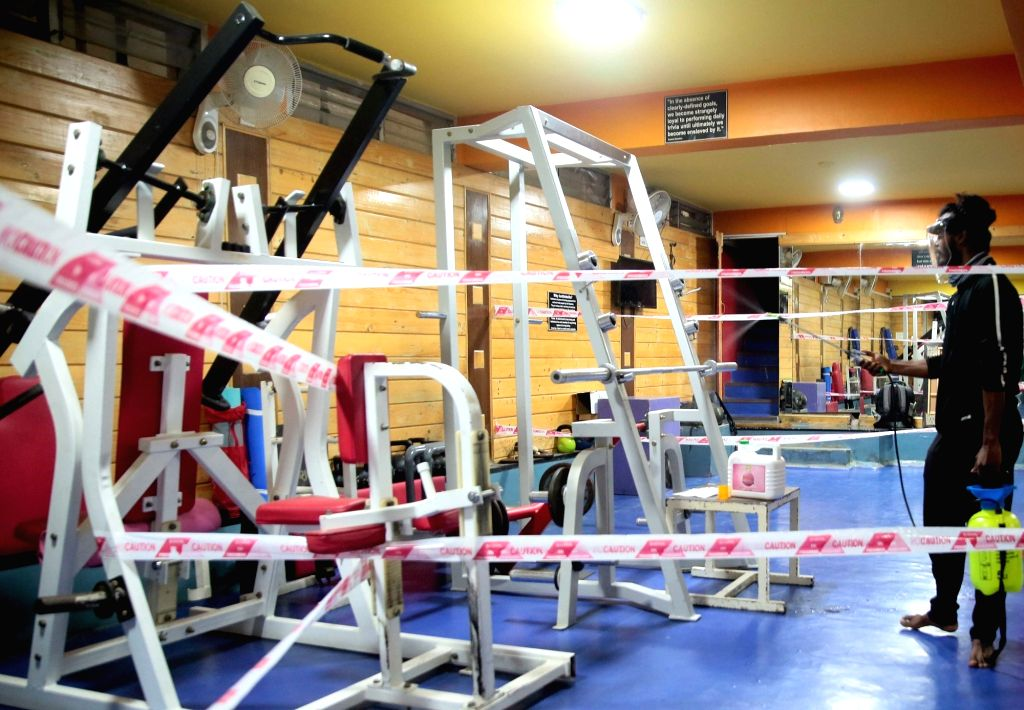 Workout equipments being sanitised at a gym as yoga institutes and gymnasiums are slated to open from tomorrow i.e August 5 as a part of the third phase of easing of COVID-19 lockdown, in ...