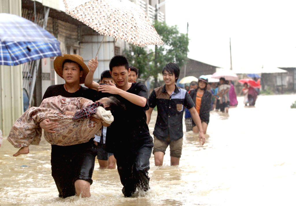 Rescuers take an old villager to safe place in Wuchuan City, south China's Guangdong Province, Aug. 15, 2013. Three people have died and five others ...