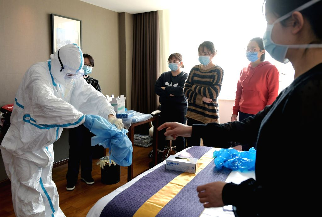 WUHAN, Jan. 30, 2020 (Xinhua) -- A medical worker from Beijing Anzhen Hospital demonstrates how to put on and take off protective clothing for preparations to join the fight against the novel coronavirus epidemic at a base for medical workers in Wuha