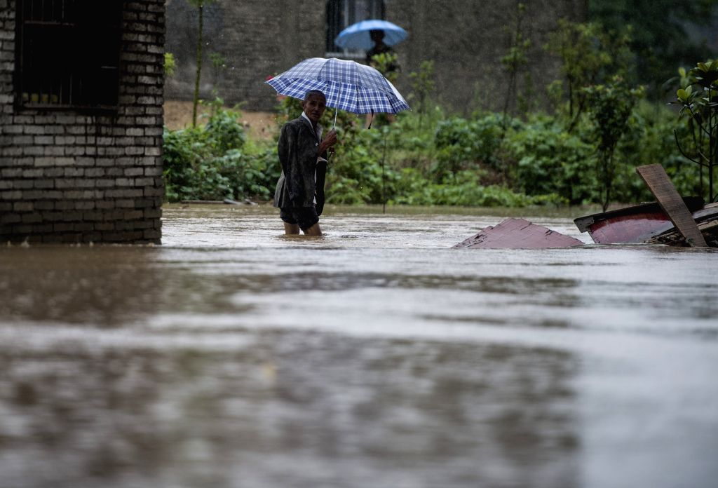 WUHAN, July 1, 2016 - A villager walks in the rain in Sanhe Village of Dawu County, central China's Hubei Province, July 1, 2016. Six people have been reported dead and four missing so far in the ...