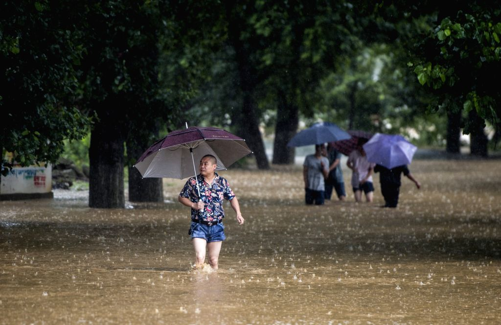 WUHAN, July 1, 2016 - Villagers walk in a waterlogged road in the rain in Sanhe Village of Dawu County, central China's Hubei Province, July 1, 2016. Six people have been reported dead and four ...