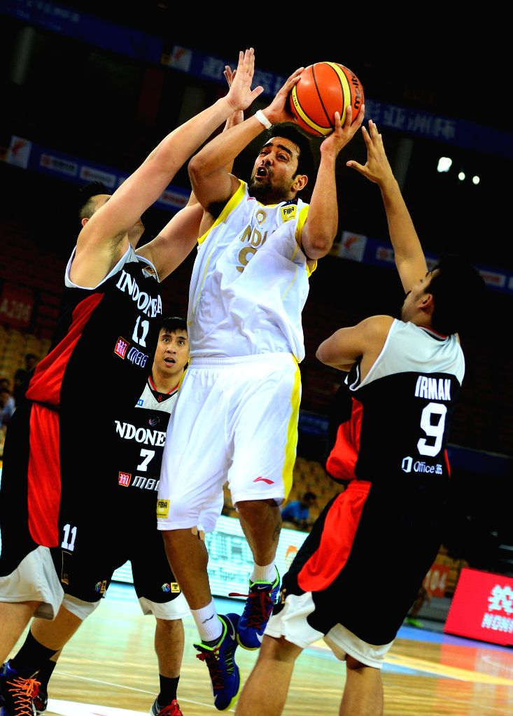 India's Vishesh Bhriguvanshi (C) goes up for a shot during the match between India and Indonesia in the 5th FIBA Asia Cup basketball tournament in Wuhan, capital of ..