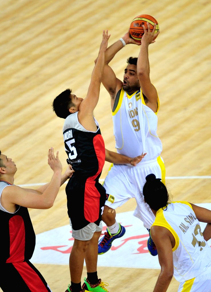 India's Vishesh Bhriguvanshi (top R) goes up for a shot during the match between India and Indonesia in the 5th FIBA Asia Cup basketball tournament in Wuhan, capital .