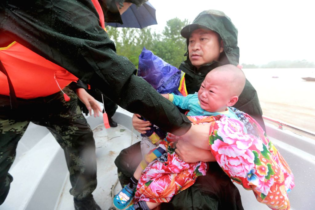 WUHAN, July 2, 2016 - Rescuers evacuate a crying baby after a dike breach in Xinzhou District of Wuhan, central China's Hubei Province, July 2, 2016. Heavy rainfall caused a dike breach on the Jushui ...