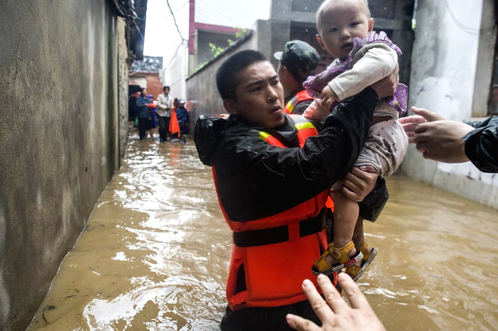 WUHAN, July 2, 2016 - Rescuers evacuate a kid after a dike breach in Xinzhou District of Wuhan, central China's Hubei Province, July 2, 2016. Heavy rainfall caused a dike breach on the Jushui River ...