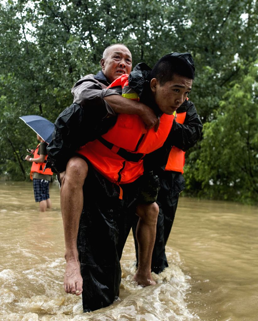 WUHAN, July 2, 2016 - Rescuers evacuate a senior villager after a dike breach in Xinzhou District of Wuhan, central China's Hubei Province, July 2, 2016. Heavy rainfall caused a dike breach on the ...