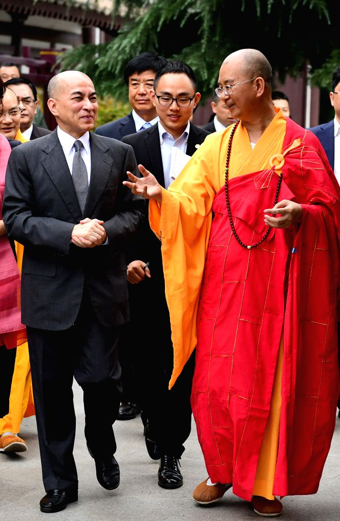 XI'Cambodian King Norodom Sihamoni (L), accompanied by Master Xuecheng (R), abbot of Famen Temple, visits the temple in Baoji City, northwest China's Shaanxi Province, ...