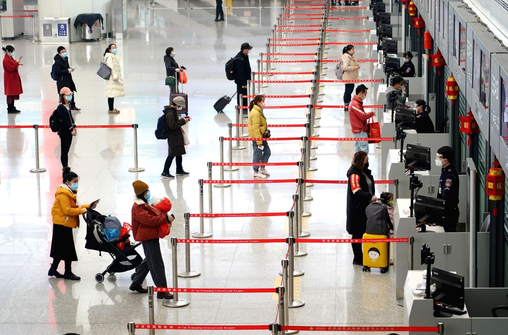 XI'Passengers line up at a certain distance before the security check at the Terminal 3 of Xianyang International Airport in Xi'an, northwest China's Shaanxi Province, ...