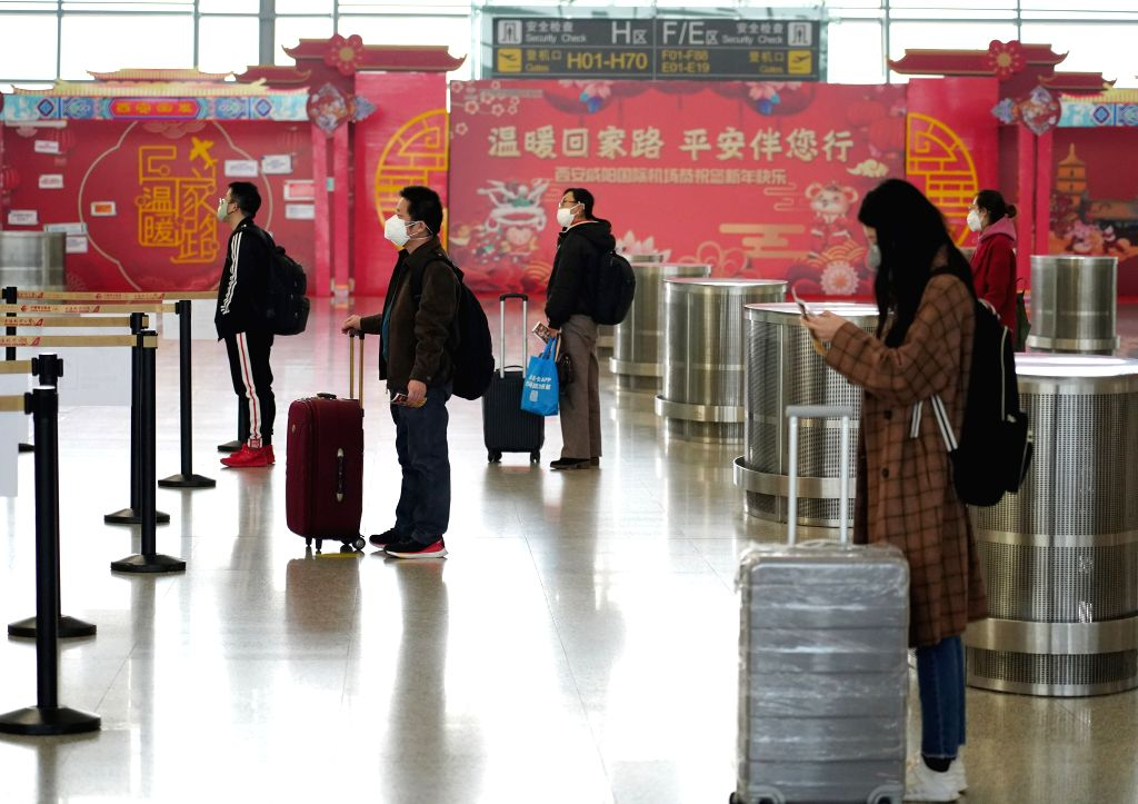 XI'Passengers line up at a certain distance before checking-in at the Terminal 3 of Xianyang International Airport in Xi'an, northwest China's Shaanxi Province, Feb. 12, ...