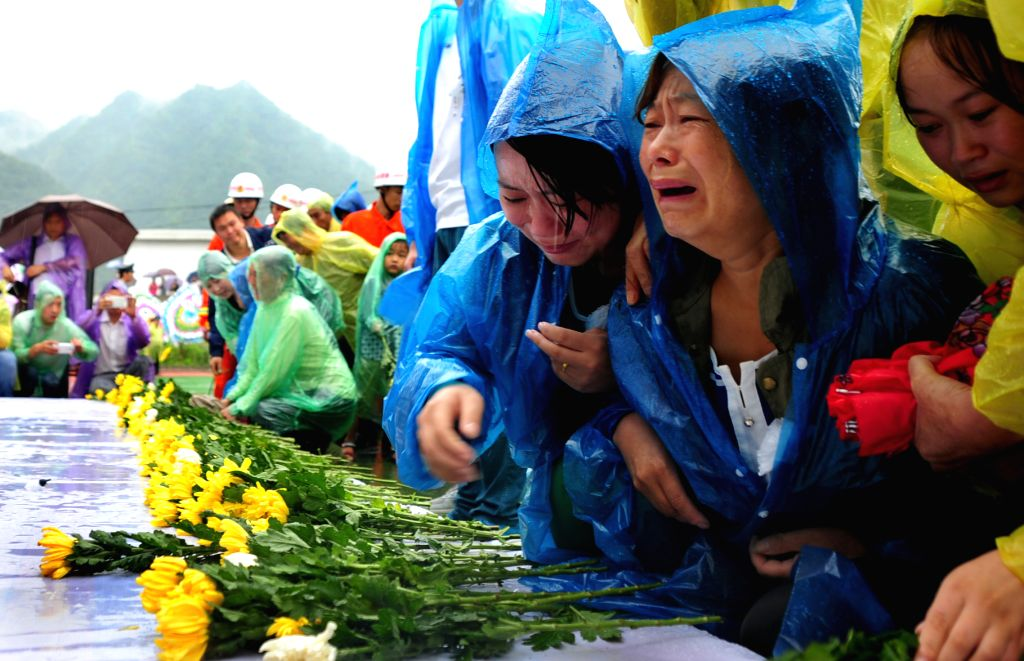 XI'People attend a mourning ceremony held for the victims of a landslide in Shanyang County, northwest China's Shaanxi Province, Aug. 18, 2015. A landslide hit the ...