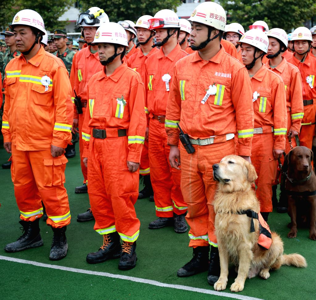 XI'Rescuers attend a mourning ceremony held for the victims of a landslide in Shanyang County, northwest China's Shaanxi Province, Aug. 18, 2015. A landslide hit the ...