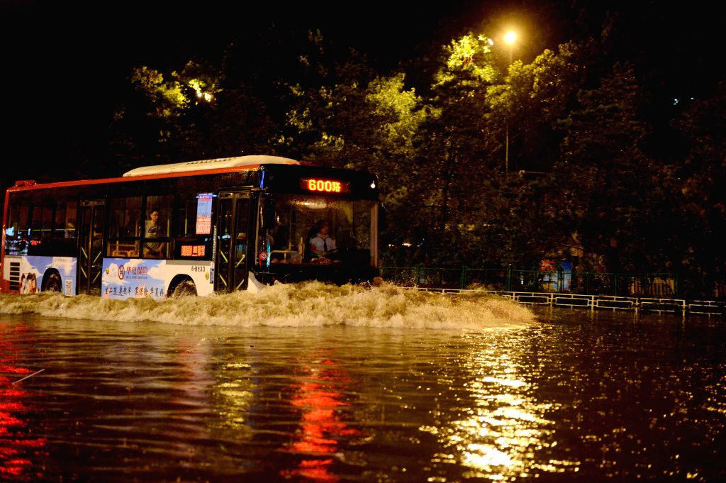 ?XI'Residents push a car stranded on a flooded road in Xi'an, capital of northwest China's Shaanxi Province, July 24, 2016. The city's meteorological bureau issued a red ...