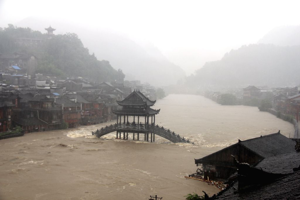 Shops along the Tuojiang River have been inundated in Fenghuang County of central China's Hunan Province, July 15, 2014. More than 120,000 locals and tourists have .