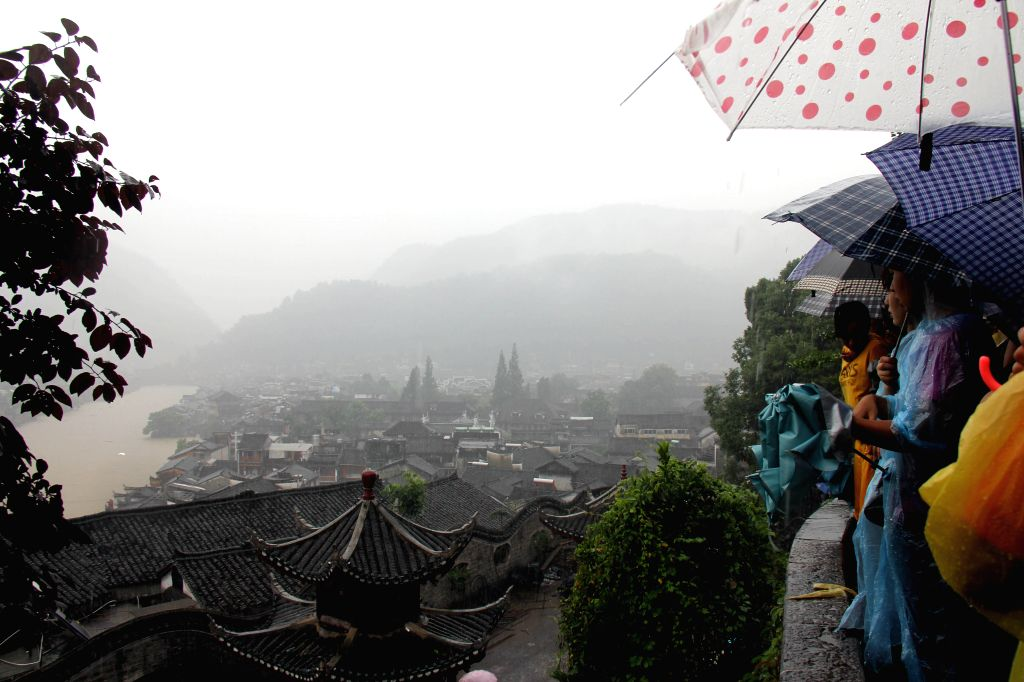 Tourists shelter from the rain in Fenghuang County of central China's Hunan Province, July 15, 2014. More than 120,000 locals and tourists have been evacuated since