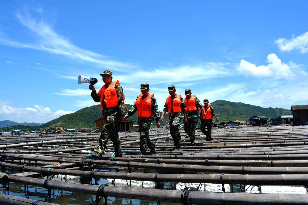 Border policemen inform fishermen of the approach of Typhoon Matmo in Xinan Town of Xiapu County, southeast China's Fujian Province, July 22, 2014. Typhoon Matmo, the