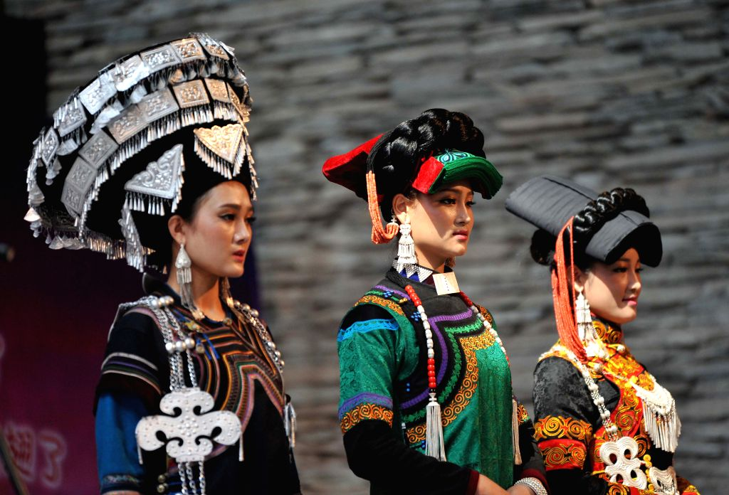 Women of the Yi ethnic group present their folk costumes during a traditional beauty contest at Xichang City, southwest China's Sichuan Province, July 23, 2014. The