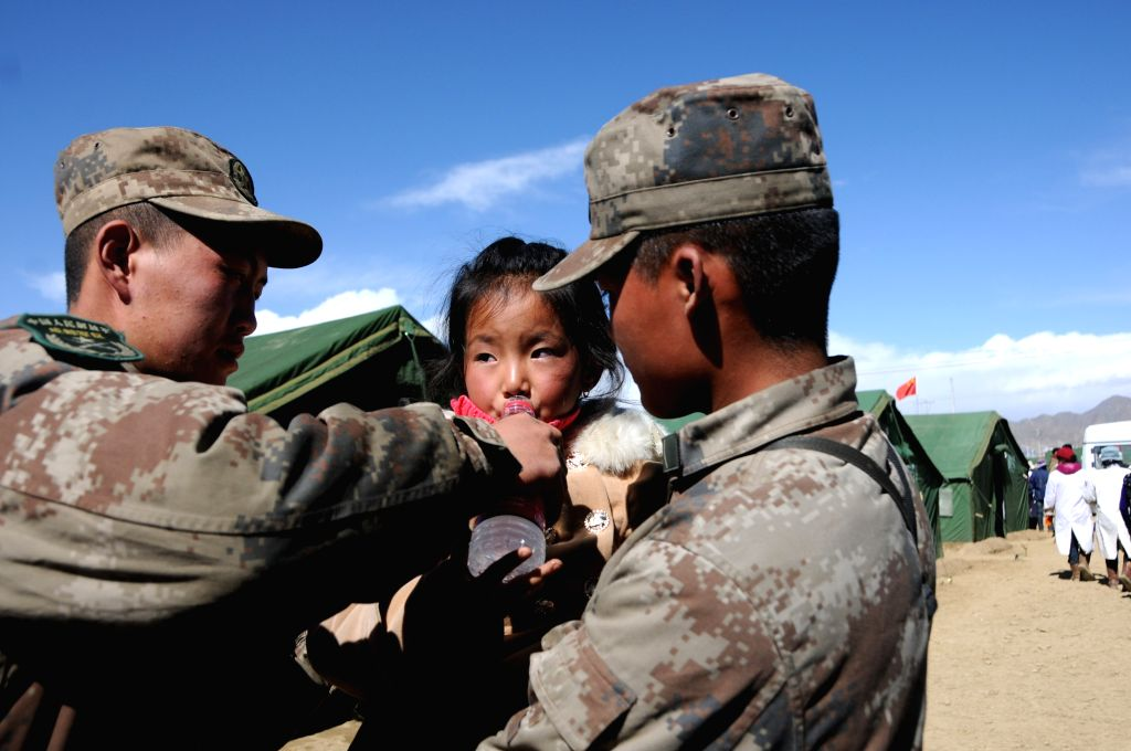 Soldiers help a girl to drink at a settlement in an industry zone in Xigaze, southwest China's Tibet Autonomous Region, April 30, 2015. A total of 3,500 makeshift ...
