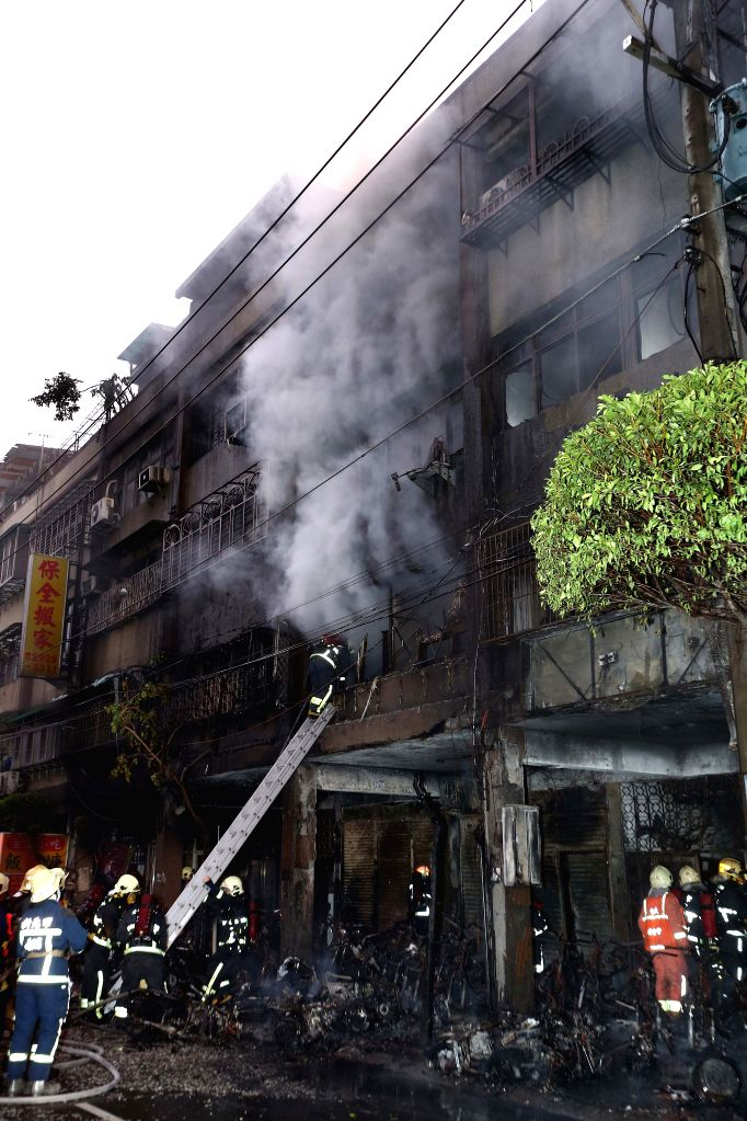 Firefighters try to put out fire in a residential building in Xinbei City, southeast China's Taiwan, Sept. 12, 2014. The fire left 25 people injured. One of them ...